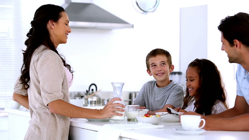 Mother chatting to children at family breakfast and pouring milk in the kitchen at home