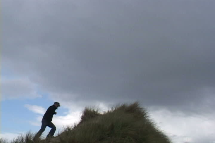 Man runs up sand dune and looks out at the view. - SD stock video clip