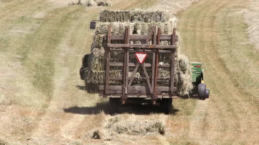 Tractor Pulled Wagon : Hay wagon with load being pulled away by tractor and baler