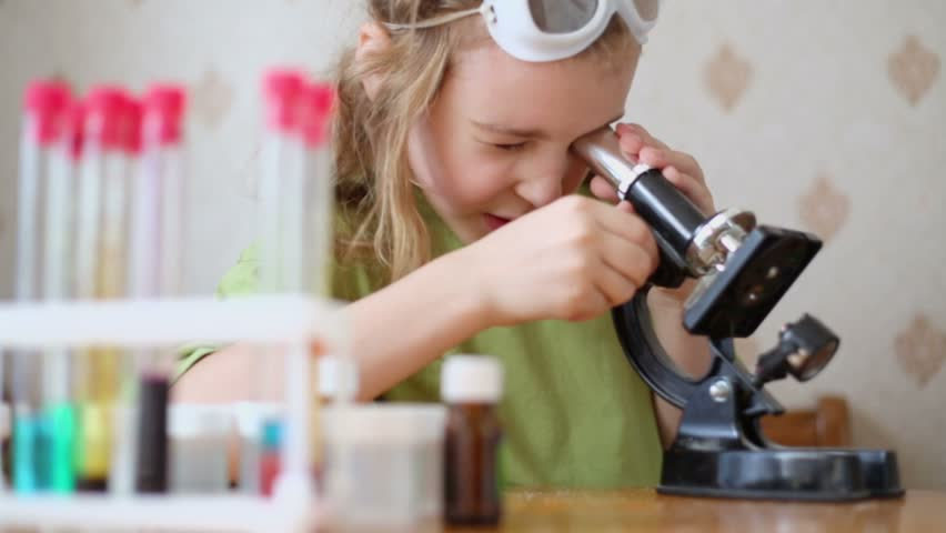 Little girl attentively looks into microscope on table with chemical glassware - HD stock video clip