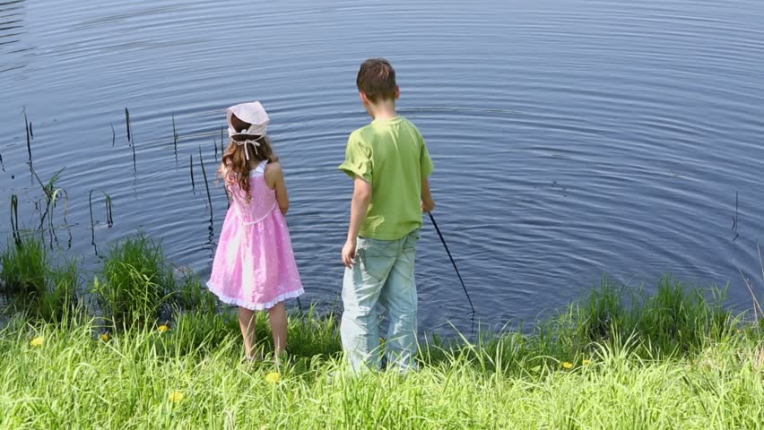 Two kids boy and little girl stand near pond and play with for Children s fishing rod