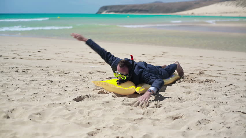 Businessman swimming on the beach with inflatable mattress and wearing snorkeling mask