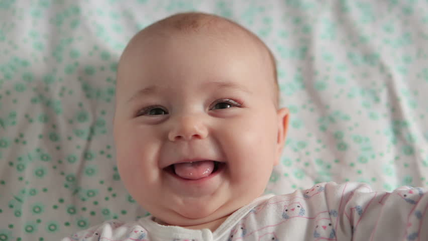 Cute baby lies on back and smiling (closeup)