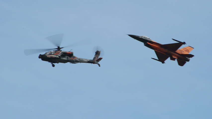 VOLKEL, NETHERLANDS - June 14 2013: Apache AH-64 Helicopter and a F-16 Fighting Falcon fly together, the Apache performina a looping during an airshow at Volkel, Netherlands, June 14, 2013