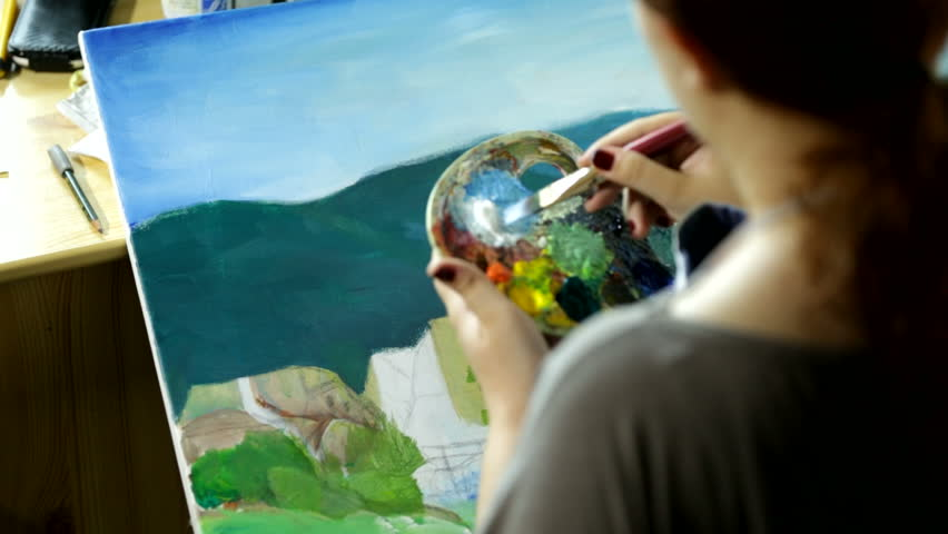 Professional artist working on a nature landscape, painting it with watercolors on canvas. Woman using palette and different brushes.