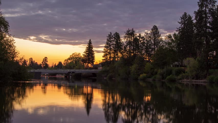 Time Lapse of Morning Sunrise shinning on the thick Clouds above a small park in Bend, Oregon. Pink and Orange color blending into the clouds as the sun rising. Color also reflected onto the water.
