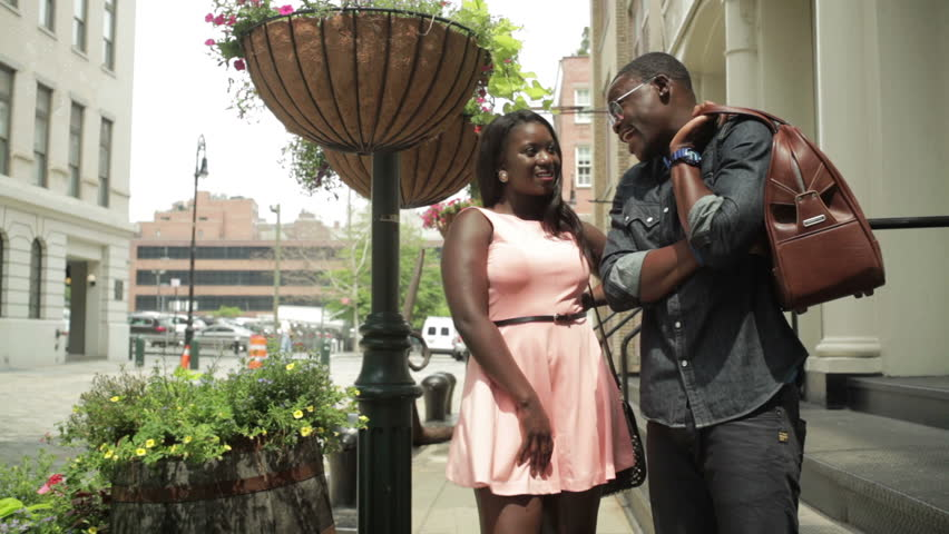 Happy young black couple talking in the street