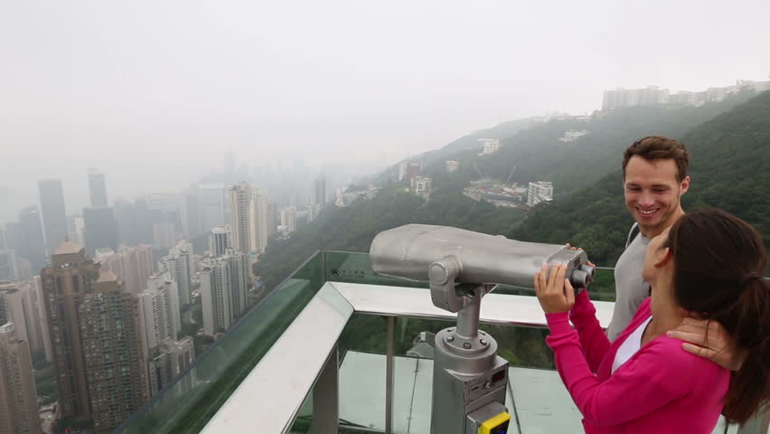 Hong Kong Victoria Peak tourists romantic couple enjoying view looking in binoculars over Hong Kong Island and Victoria Harbour. Young happy multiethnic couple traveling in Hong Kong. Travel concept. | Shutterstock HD Video #4185860