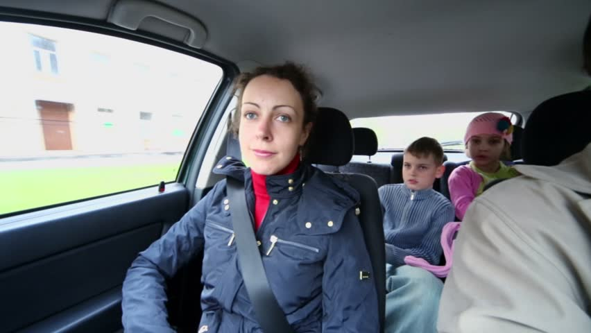 Family of four drive in car, children sit on backseat, (panoramic motion) - HD stock video clip