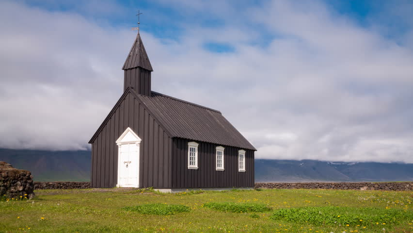 Timelapse of black wooden church in front of a mountain range in Budir, Iceland