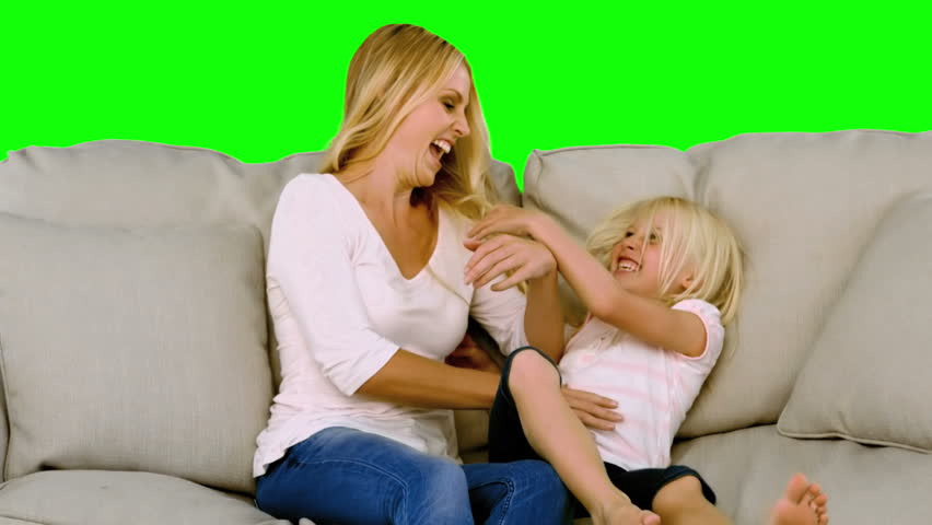 Mother tickling her daughter in slow motion on green screen