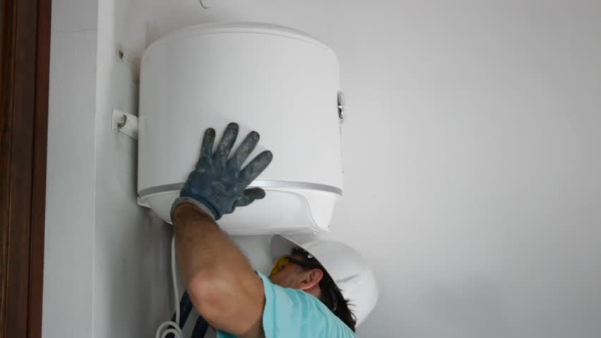 plumber installing an electric water heater - HD stock footage clip