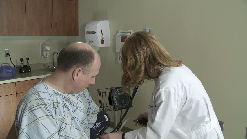 Medium shot of female doctor taking the blood pressure of a mature male patient. - HD stock footage clip