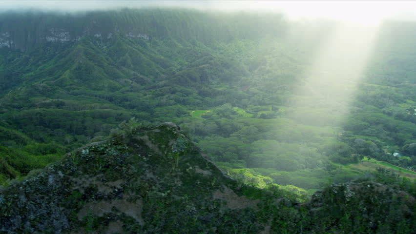 Aerial view of sun rays on volcanic cliffs covered in rich fertile tropical landscape, Hawaii, Oahu, USA, RED EPIC