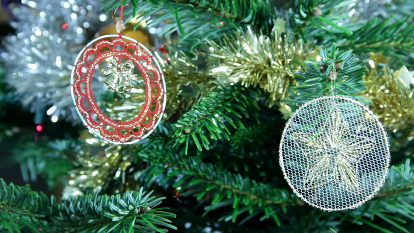 Close up of two lace Christmas tree decorations: a white roundel with star motif, the second red with bells set in the centre. Both hanging on a Christmas tree decorated with green and silver tinsel. #4261766