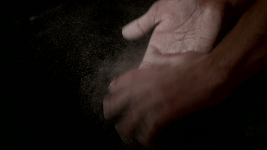 Two hands covered in chalk slap against each other, knocking white dust