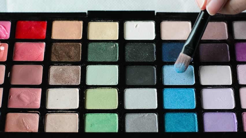 Woman is brushing eye shadow palette in closeup - HD stock video clip