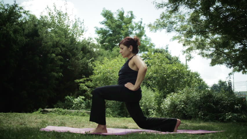 woman working out doing lunge exercise in the park on a yoga mat