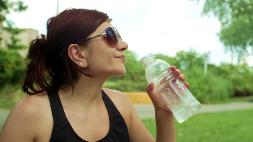 Thirsty young woman with sunglasses drinking water from a bottle in the park on a sunny hot day in the summer | Shutterstock HD Video #4273799