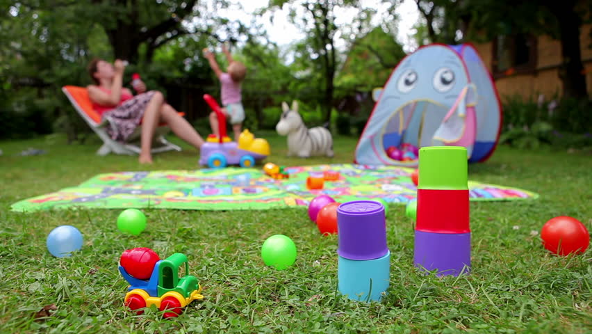 HD 1080p: Toys on grass and unrecognizable baby and mother on background with soap bubbles (dolly shot)