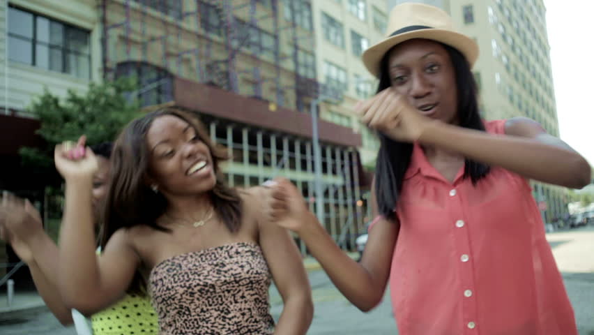 3 teenage girls dancing outdoor having a party in the street smiling and happy outside on a sunny day