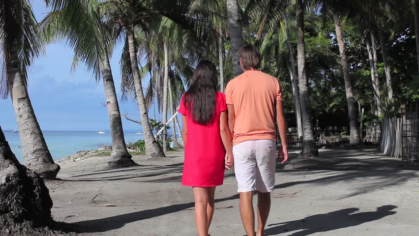 Romantic couple walk at tropical beach near palm tree in Philippines