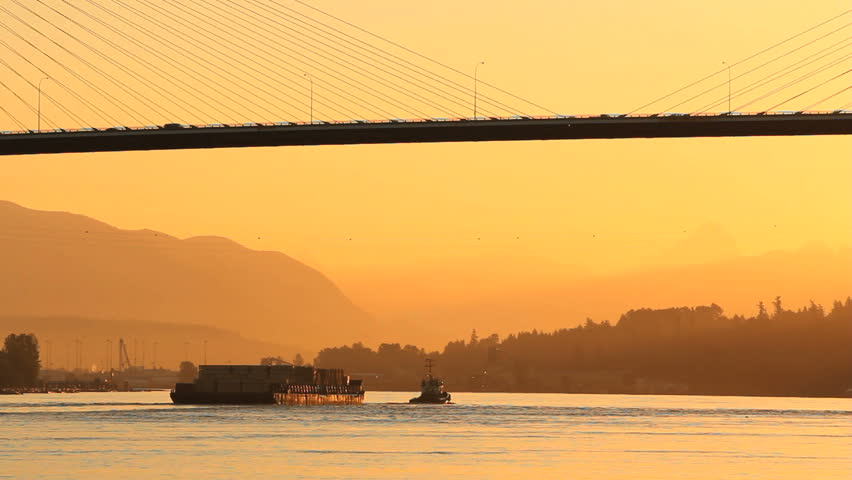 At sunrise, a tug tows a barge under the Alex Fraser Bridge on the Fraser River at Delta, British Columbia near Vancouver. Canada. Early morning commuter traffic crosses the bridge.