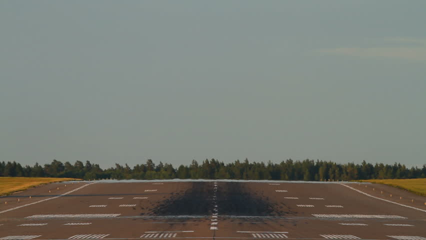 Airliner landing on a runway, close-up, straight from behind