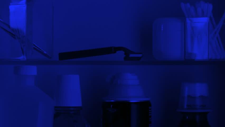Door of medicine cabinet opens, hand comes in to take razor and shaving cream,