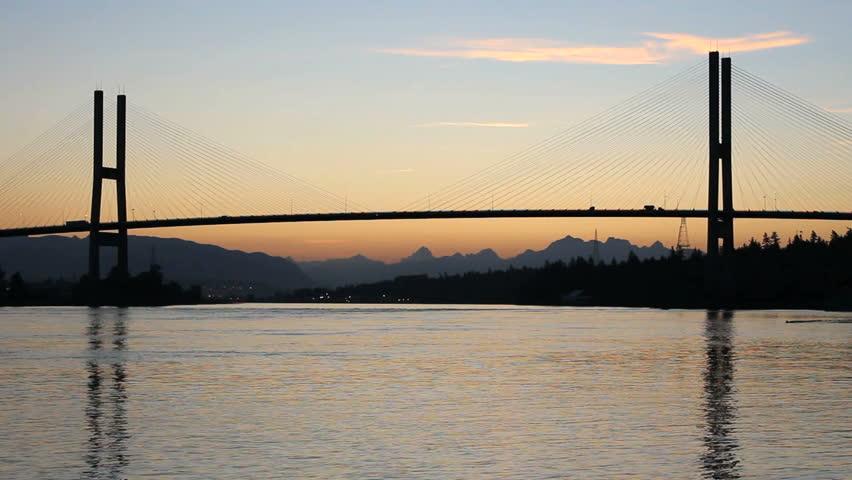 Alex Fraser Bridge Dawn. The Alex Fraser Bridge, just before sunrise, spanning the Fraser River at Delta, BC near Vancouver. Canada.  - HD stock footage clip