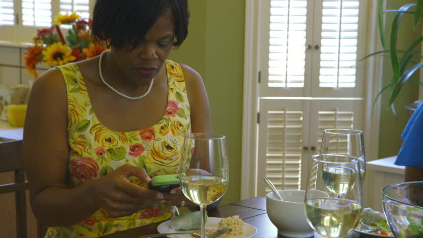 An African American woman answers emails via her cell phone while sitting at the dining table. - HD stock footage clip