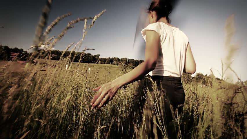 Woman walking touching long grass in field in summer - sepia style grading in slow motion