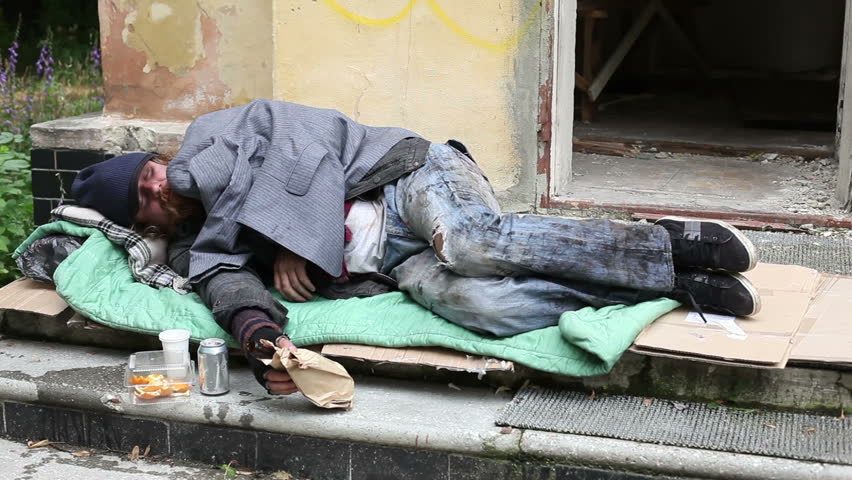 Homeless Man Sleeping In The Open Air On The Porch Of An