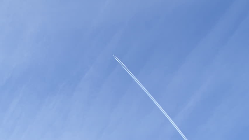 A distant airplane passes high overhead, leaving a jet contrail against a wispy blue sky - HD stock video clip