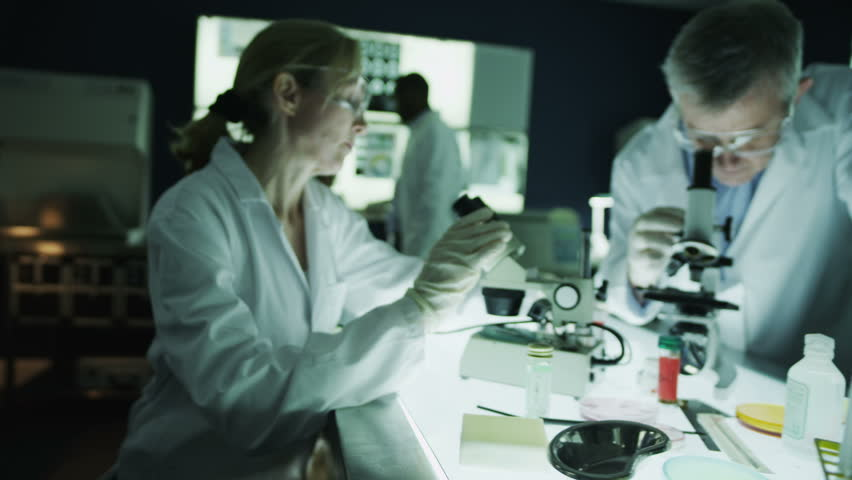 Team of scientists or researchers are working together in a dark laboratory, carrying out experiments with chemicals and a microscope. In slow motion.   Shutterstock HD Video #4362134