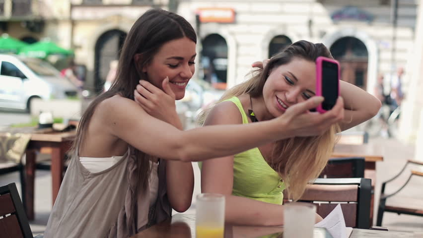 Happy girlfriends taking photo with cellphone in cafe