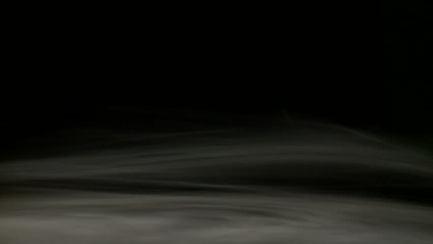 Loopable clip of a low mist, swirling against a black background.