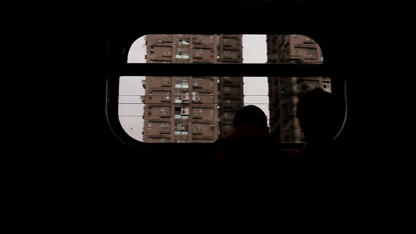 Rui Fang, Taiwan - November, 2012 - Slow motion silhouette of two kids peaking their heads up and down on the window inside of a train.