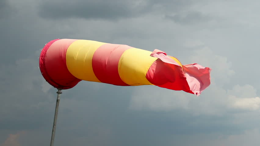 Wind sock with rainy stormy clouds background. Red and yellow