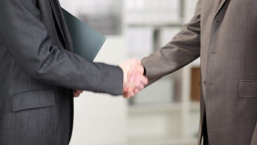 Two formal businessmen in suits shaking hands showing accord and agreement in clinching a deal, partnership or transaction - HD stock video clip