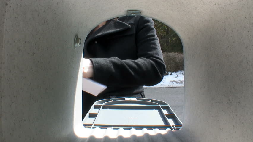 Inside the mailbox view of woman leaving a letter for the mail person to