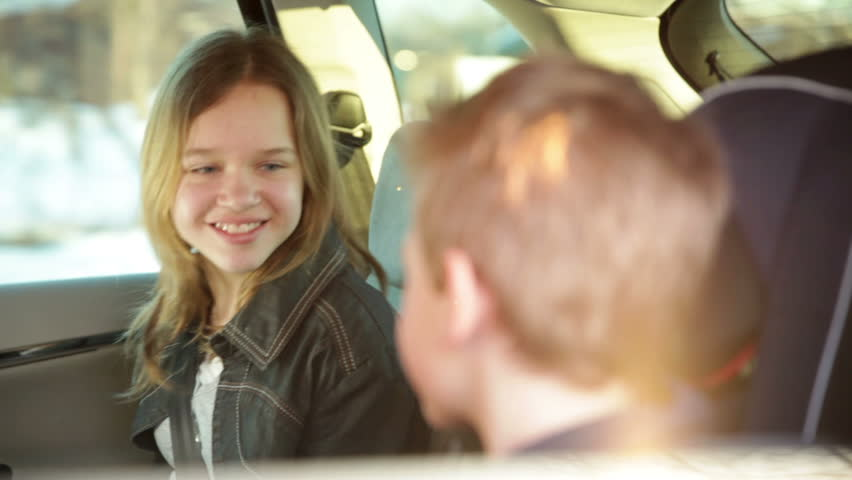 Family driving while kids in back seats are suprised by something - HD stock footage clip