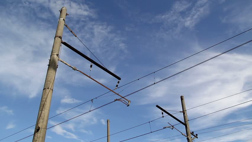 Railroad electrical wires and passing trains against blue cloudy sky - HD stock video clip