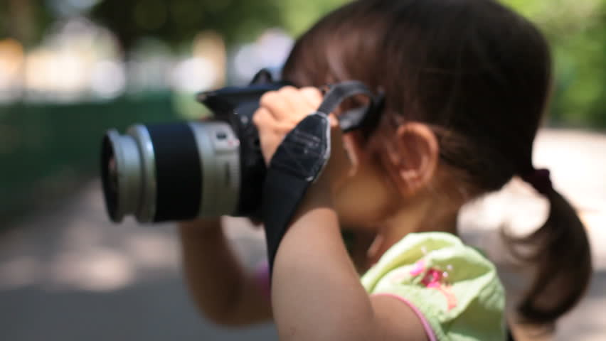 Little Baby Girl Takes Pictures With A Dslr Camera Stock