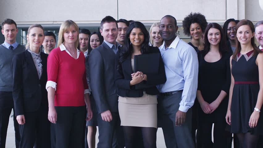 Large multi ethnic business team smile into camera. Dolly back through office following large group of business people. Team of workers in bright corporate environment.