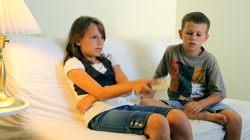 A brother and a sister fighting over who will control the remote control for the TV. - HD stock video clip