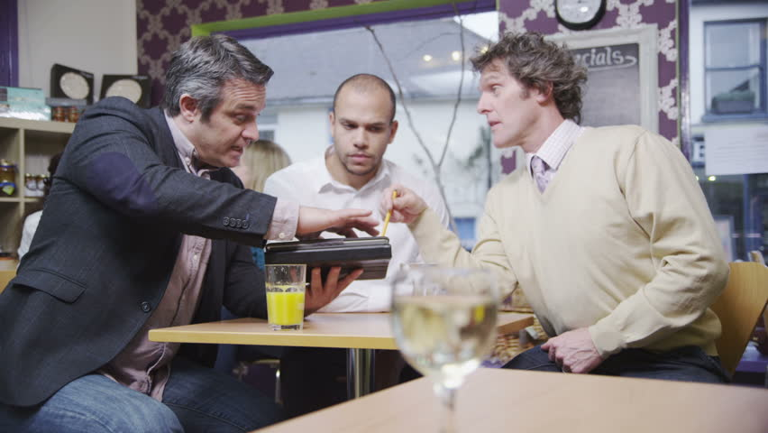 3 cheerful casual business men with a computer tablet discuss business over drinks and shake hands on a deal. In slow motion.
