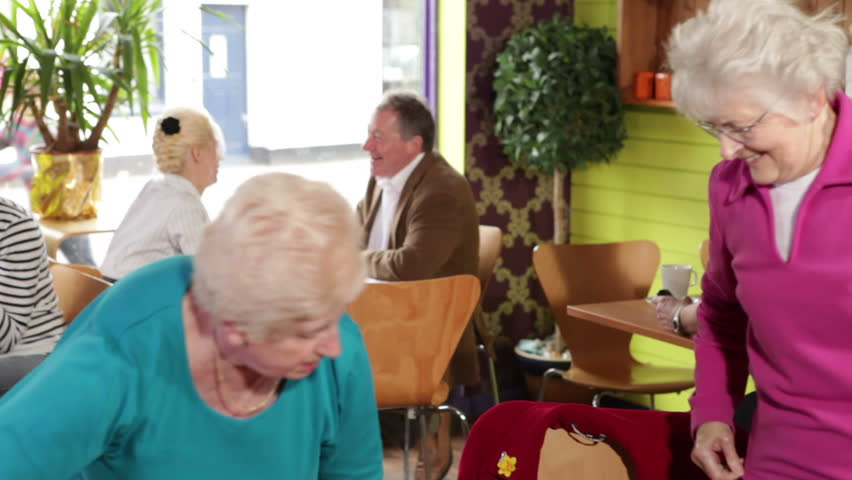 Two senior women in cafe. Group of people enjoying cafe culture and relaxing over tea and coffee. A colourful and busy restaurant serving customers. - HD stock footage clip