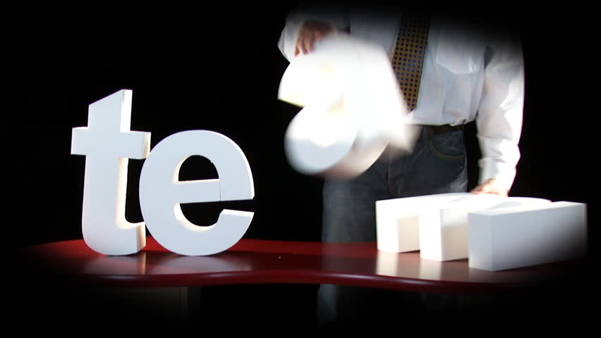 Faceless businessman in a dark room arranges large white letters to spell the word TEAM. High quality HD video footage