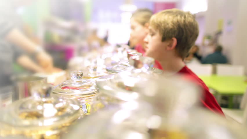 Children in a candy store exploring a variety of jars containing sweets, candy and chocolates.